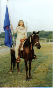 Alyse riding Dream Catcher carrying the Youth Flag